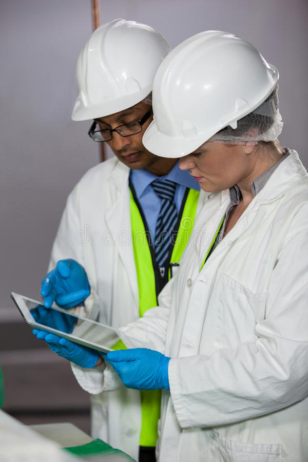 Technicians looking at digital tablet. In meat factory stock photography