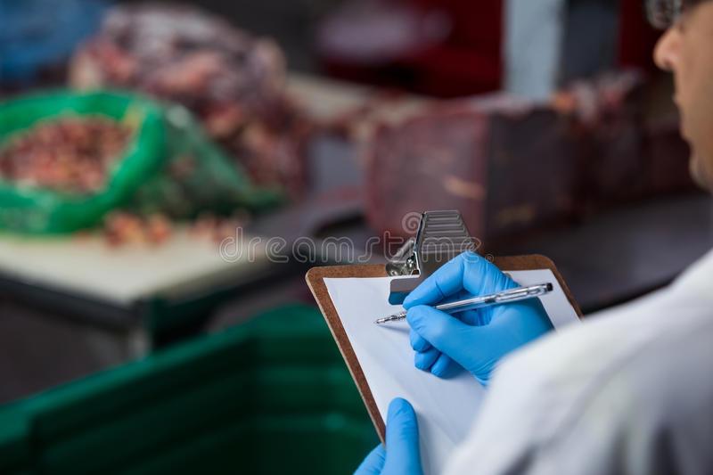 Technicians maintaining records on clipboard. At meat factory stock photos