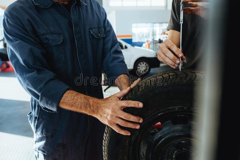 Technicians measuring the depth of tire tread instrument. Two technicians checking the depth of tire tread with measuring instrument. Mechanics inspecting the royalty free stock photos