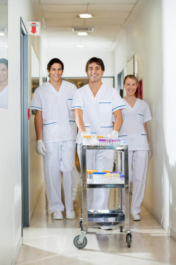Download Technicians With Medical Cart Walking In Corridor Stock Image - Image: 37136905