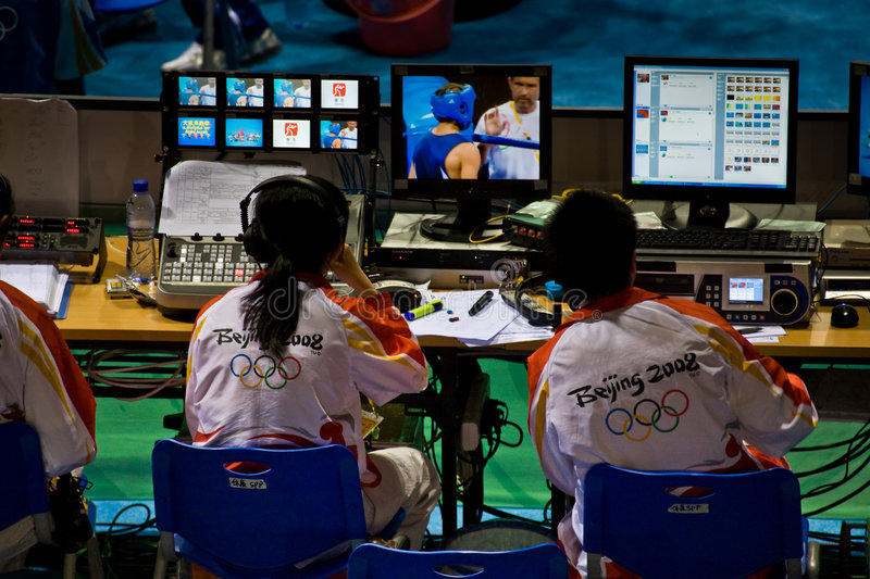Technicians monitor the Olympic broadcast. TV crew monitors the camera feeds for the broadcast of Olympic boxing in Beijing China stock image