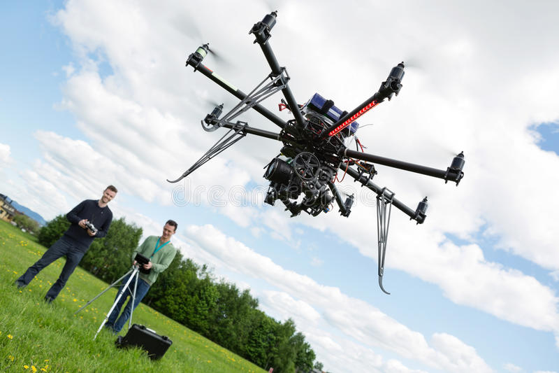 Technicians Operating UAV Helicopter in Park. UAV helicopter flying while male technicians operating it in park stock photography