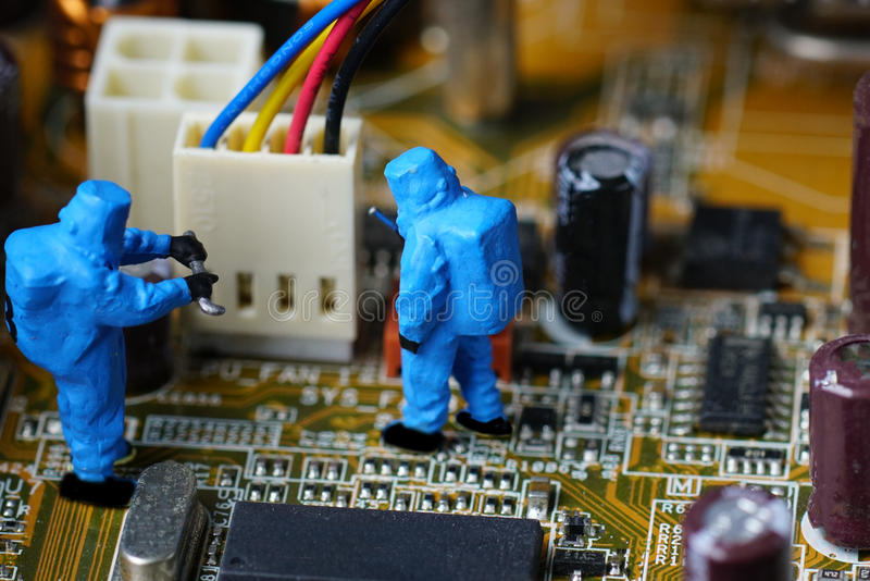Technicians repair on computer mainboard. Miniature people stock photos
