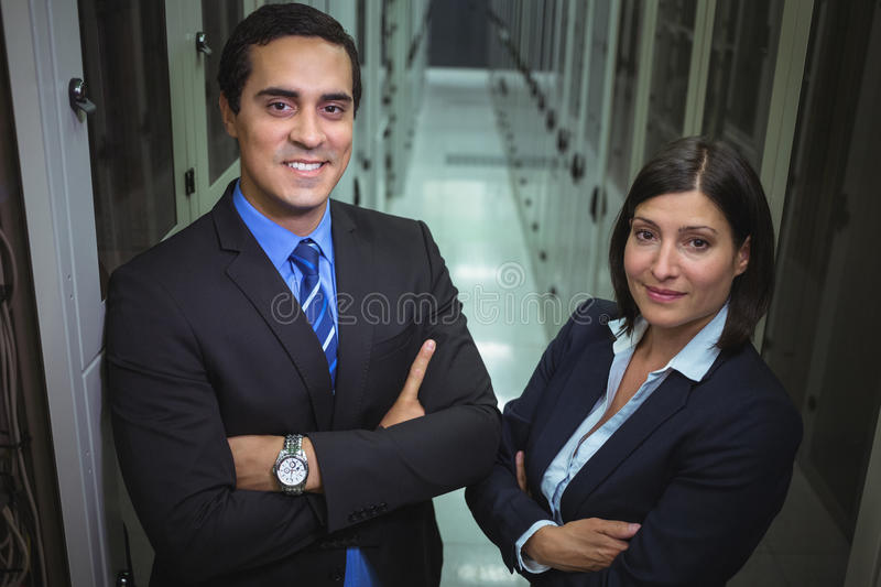 Technicians standing with arms crossed in a server room. Portrait of technicians standing with arms crossed in a server room stock photo