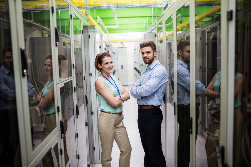 Technicians standing with arms crossed in a server room. Portrait of technicians standing with arms crossed in a server room stock photography