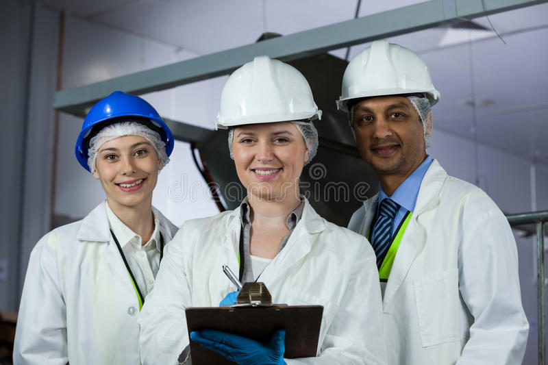 Technicians standing with a clipboard. In meat factory royalty free stock image