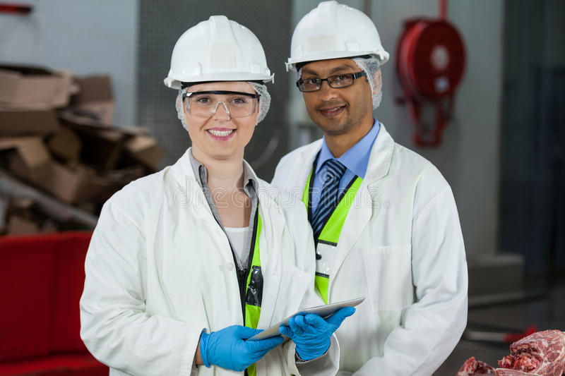 Technicians standing in meat factory. Portrait of smiling technicians standing in meat factory royalty free stock photos