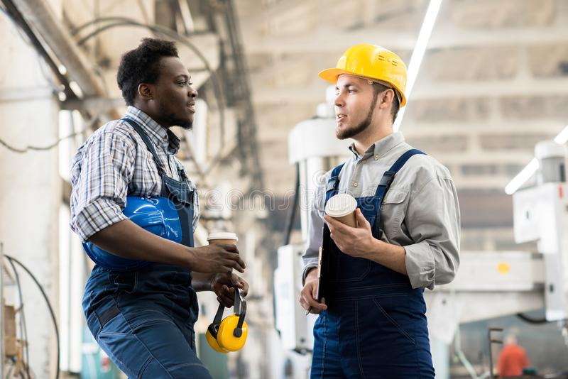 Technicians Taking Coffee Break. Multi-ethnic team of technicians wearing overalls chatting animatedly with each other while taking coffee break, interior of stock images