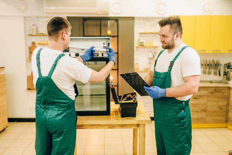 Technicians in uniform repair refrigerator at home. Two technicians in uniform repair refrigerator at home. Repairing of fridge occupation, professional service royalty free stock photography