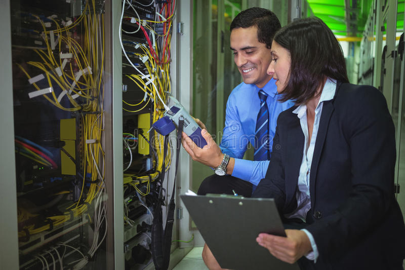 Technicians using digital cable analyzer while analyzing server. In server room royalty free stock photos