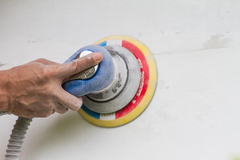 Technicians are using a hand polish machine to scrub to smooth plaster walls. royalty free stock image