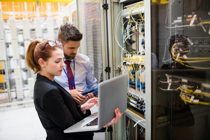 Technicians using laptop while analyzing server. In server room stock image