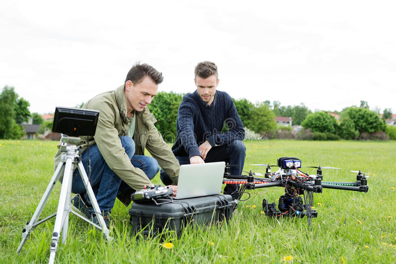 Technicians Using Laptop By Tripod And UAV. Young male technicians using laptop by tripod and UAV octocopter in park stock images