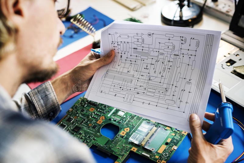 Technicians working holding electronics circuit guide paper stock photos
