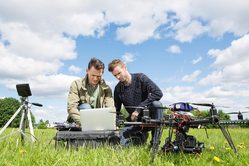 Technicians Working On Laptop By UAV in Park. Young male technicians working together on laptop by UAV helicopter and tripod in park stock image