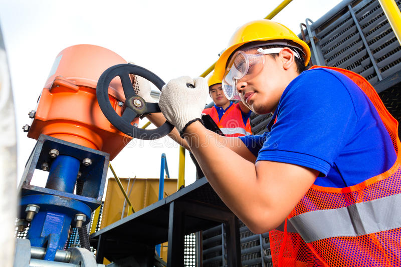 Technicians working on valve in factory or utility. In utility or factory ewo technicians or engineers working on a valve on building technical equipment or royalty free stock images
