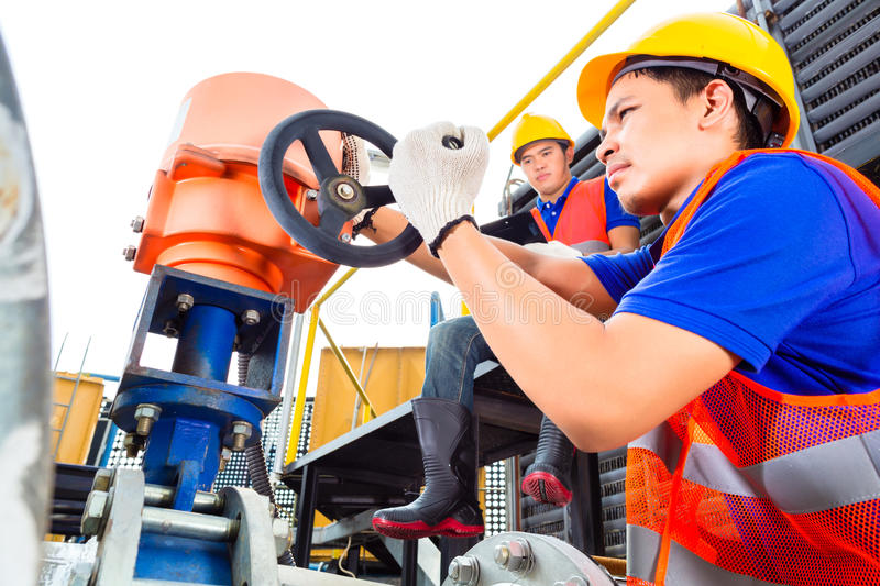 Technicians working on valve in factory or utility royalty free stock photography