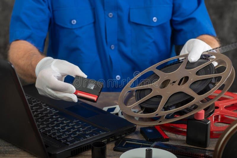 Technicien avec les gants blancs digitalisant le vieux film 16mm et DV photographie stock