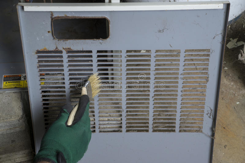 Technicien Cleaning Front Cover Of Furnace photographie stock libre de droits