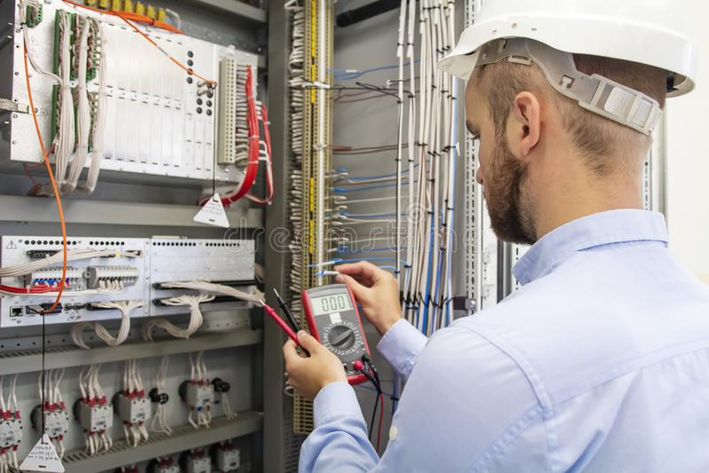 Technicien d'électricien dans la boîte de fusible Ingénieur d'entretien dans le panneau de commande Le travailleur examine l'équi photo libre de droits