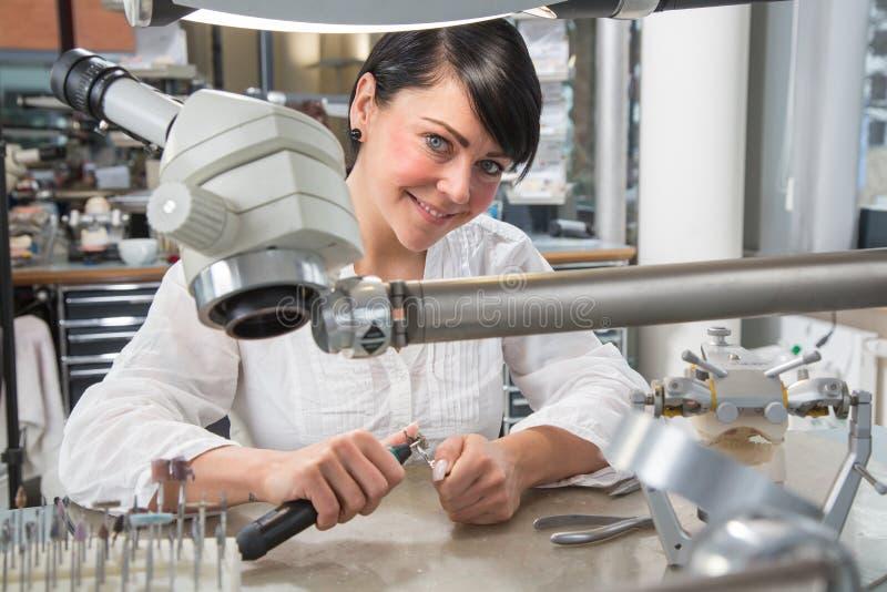 Technicien dans un laboratoire ou un atelier dentaire fonctionnant sous un microscope photos libres de droits