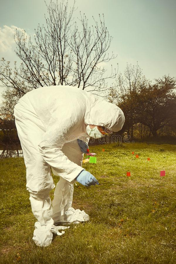 Technicien de criminaliste dans travailler global protecteur stérile d'ADN à la découverte des preuves dans le terrain avec des d images libres de droits