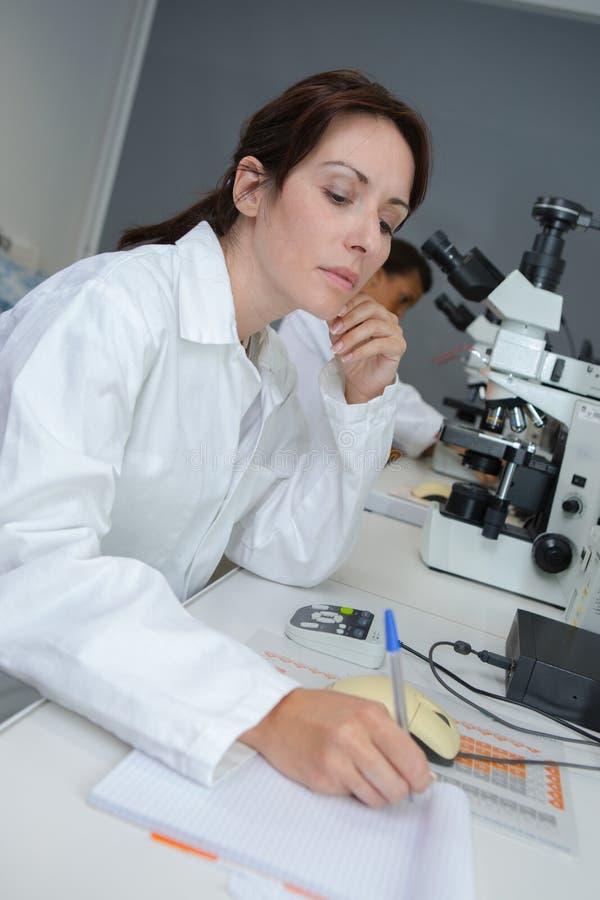 Technicien de laboratoire faisant des notes image libre de droits