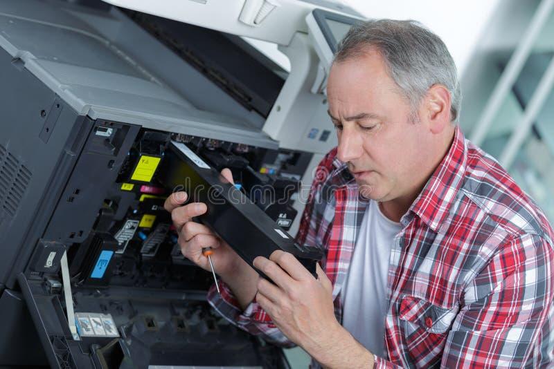 Technicien de sourire s'asseyant près du copieur image libre de droits
