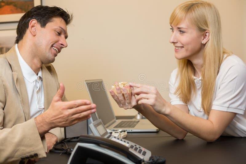 Technicien dentaire affichant la prothèse à un propriétaire photos stock