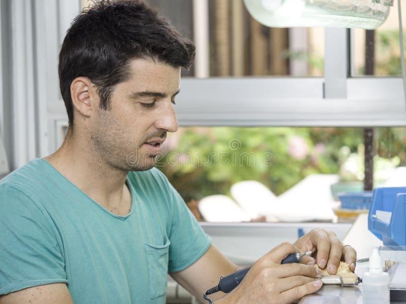 Technicien dentaire modelant une dent en céramique d'implant avec un dril photo libre de droits