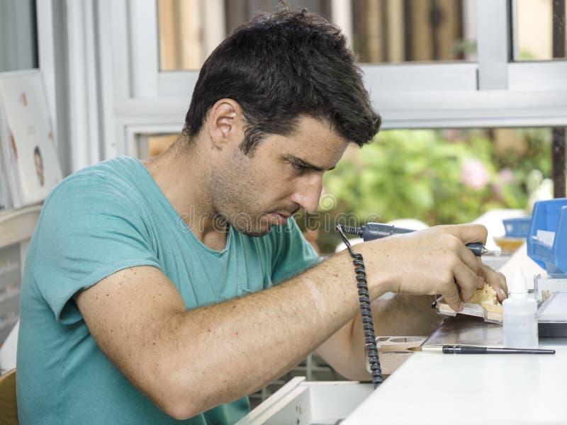 Technicien dentaire modelant une dent en céramique d'implant avec un dril photographie stock