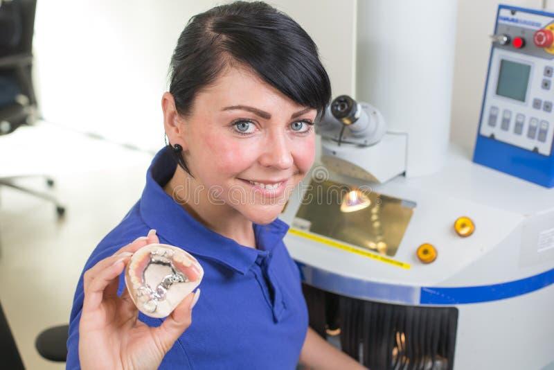 Technicien dans un laboratoire dentaire présentant une prothèse dans l'appareil-photo image stock