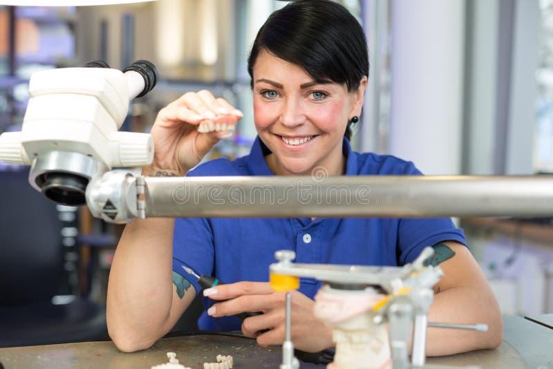 Technicien dans un laboratoire dentaire présentant une prothèse dans l'appareil-photo photographie stock libre de droits