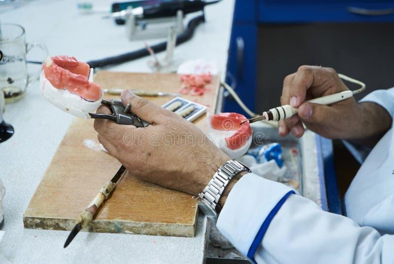 Technicien dentaire utilisant un couteau avec les implants dentaires en céramique photo libre de droits