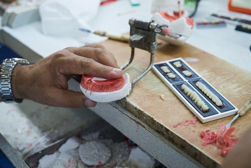 Technicien dentaire utilisant un couteau avec les implants dentaires en céramique photographie stock