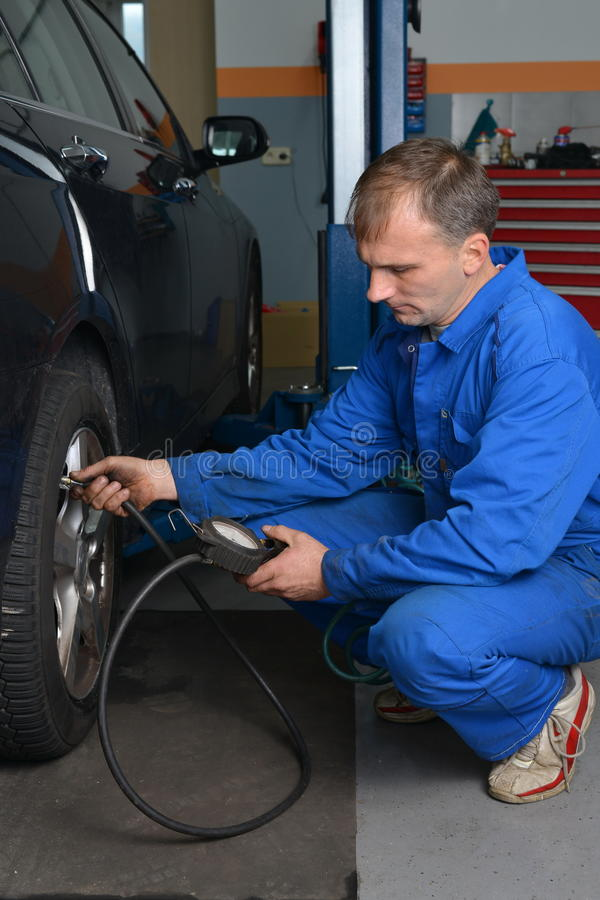 Technicien automatique de service vérifiant la pression des pneus photo libre de droits