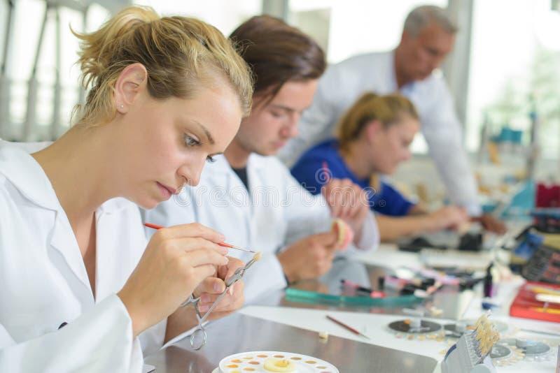 Technicien féminin ajoutant la couleur à la dent fausse photo libre de droits