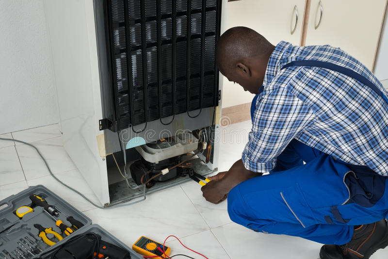 Technicien Fixing Refrigerator With Worktool image stock