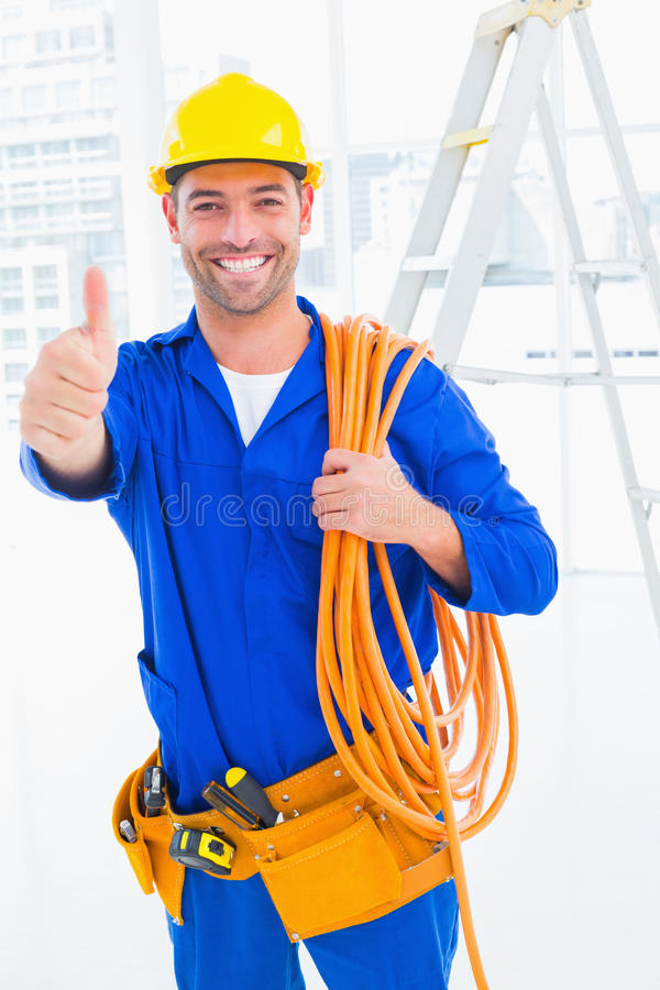 Technicien masculin avec le petit pain de fil faisant des gestes des pouces  photo stock