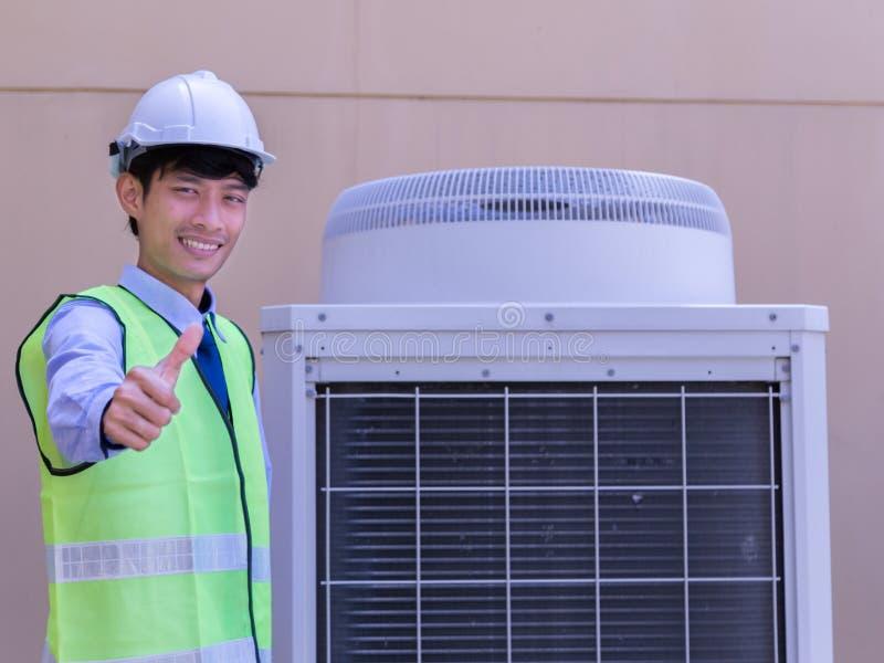 Technicien masculin heureux Repairing Air Conditioner avec le tournevis photographie stock libre de droits