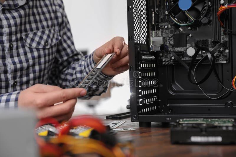Technicien masculin r?parant l'ordinateur ? la table photographie stock