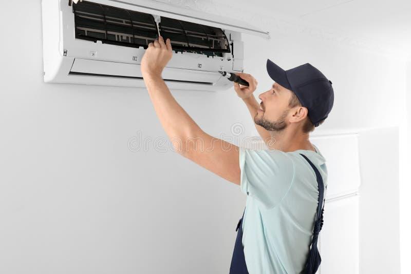 Technicien masculin réparant le climatiseur image libre de droits