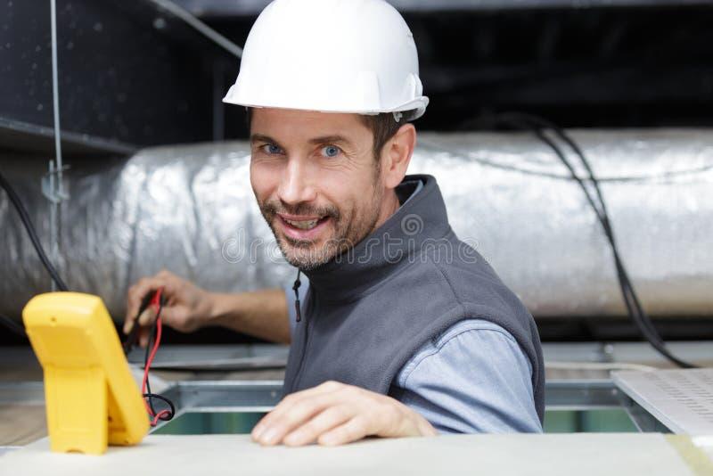 Technicien masculin réparant le climatiseur industriel à l'intérieur photographie stock