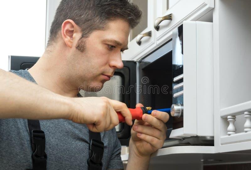 Technicien masculin réparant le four à micro-ondes image stock
