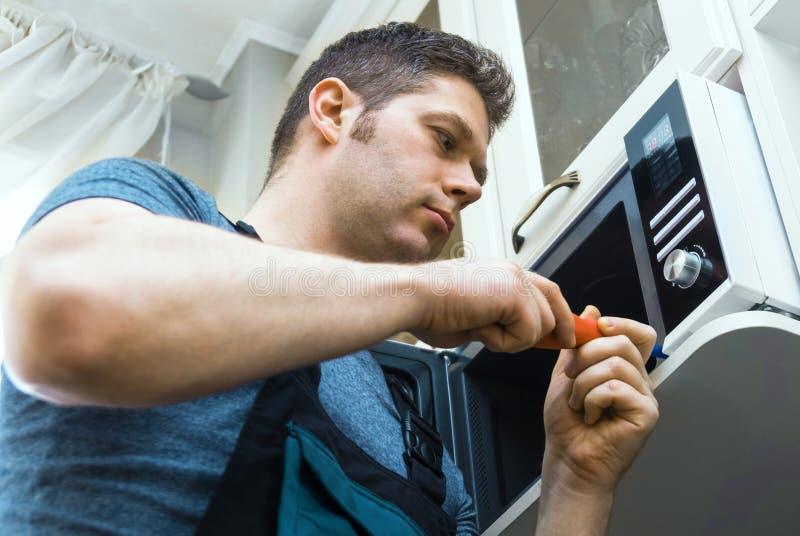 Technicien masculin réparant le four à micro-ondes image libre de droits