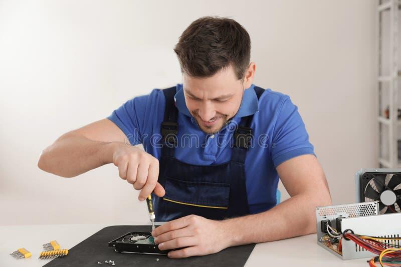 Technicien masculin r?parant l'unit? de disque dur ? la table photographie stock libre de droits