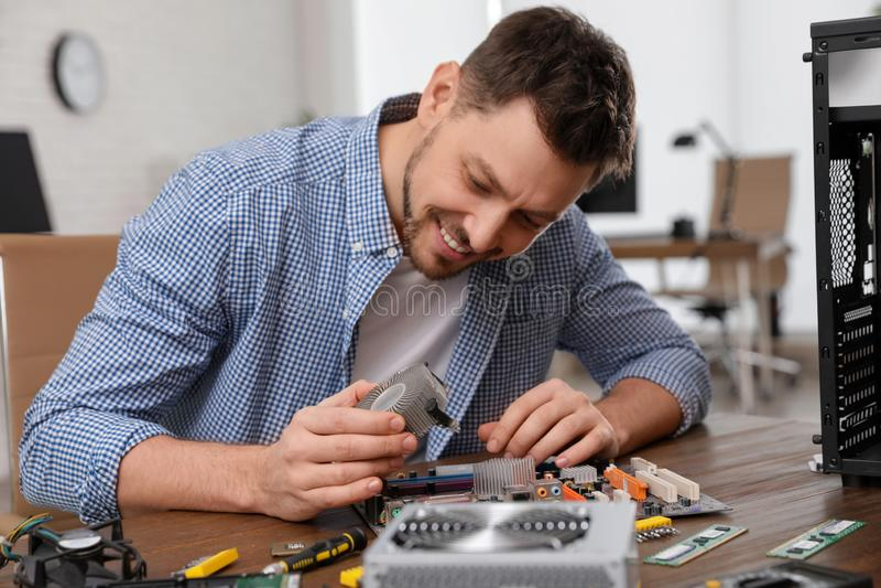 Technicien masculin r?parant la carte m?re ? la table images stock