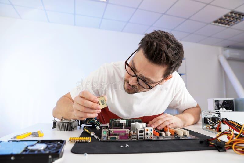 Technicien masculin r?parant la carte m?re ? la table photos libres de droits