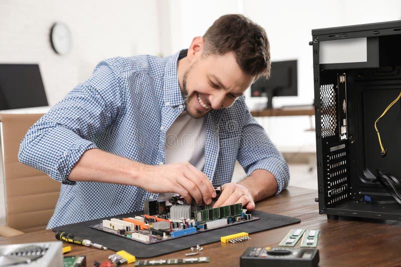 Technicien masculin r?parant la carte m?re ? la table photographie stock libre de droits