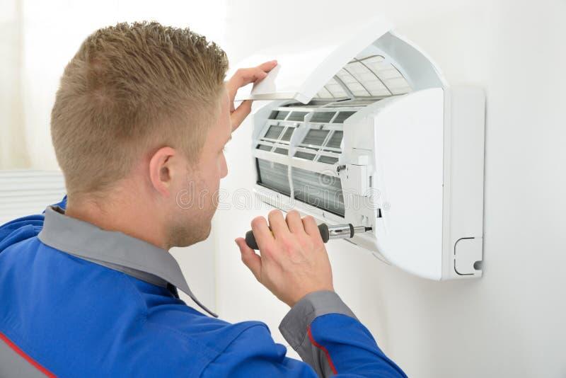 Technicien réparant le climatiseur photographie stock libre de droits